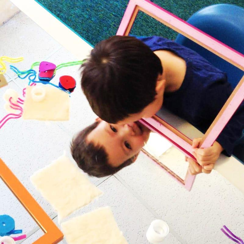 boy looking in mirror at preschool