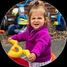 girl ridding trike at preschool