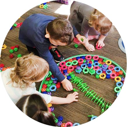 children at daycare completing puzzle