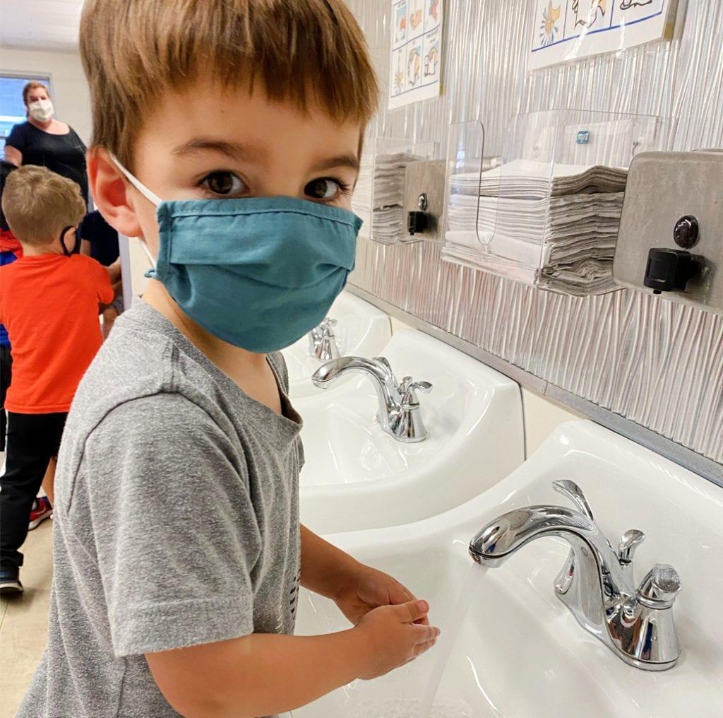 preschool boy washing hands